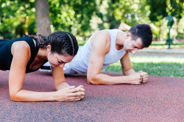 Woman and man doing plank exercise