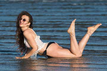 Woman with long curly hair wear bottom bikini, sunglasses and white shirt, lying in sea water