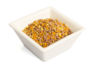 Bee pollen in the bowl closeup isolated on white background