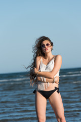 Woman with long curly hair wear bottom bikini, sunglasses and white shirt, standing in sea water. Sea and sky as background