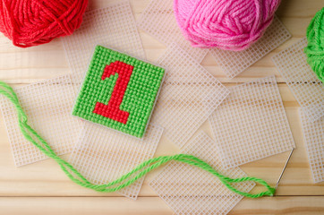 Plastic Canvas, hand made with red yarn number on wooden backgro