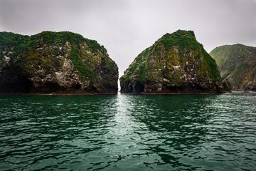 Green rocky cliffs form the coastline of the Avacha Bay, Kamchatka, Russia