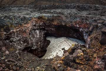 Lava pit between lava streams filled with snow, Tolbachik Volcano, Kamchatka, Russia