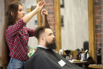 Side view portrait of handsome young bearded caucasian man getting trendy haircut in modern barber shop. Attractive hairstylist girl working, serving client, doing haircut using metal shears and comb