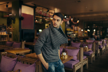 Young handsome man standing and posing in the restaurant