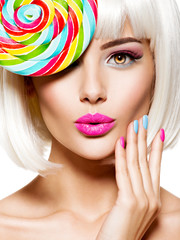 Surprised face of a pretty woman  with multicolor nails and pink