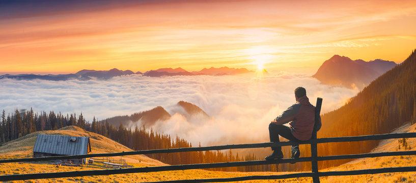 Man enjoy sunrise in a carpathian mountain valley