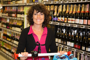 Middle aged woman shopping in the supermarket,wine shelves