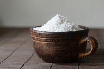 Salt in a brown ceramic bow on a wooden tablel. Rustic still life