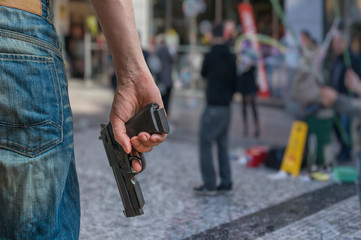Gun control concept. Armed man - attacker holds pistol in hand in public place. Many people on street.