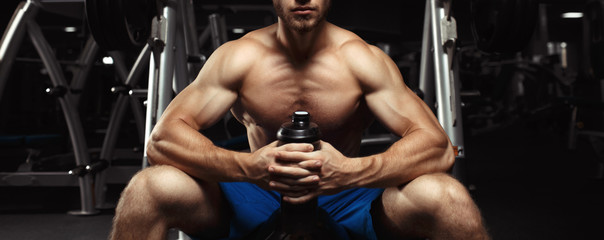 Young muscular man sitting with a bottle of water in the gym