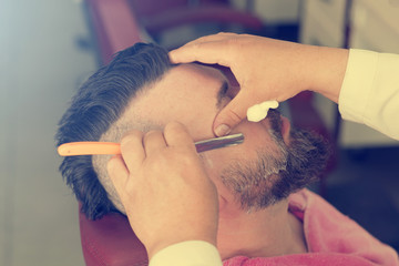 Barber with old-fashioned steel razor shaving bearded man with mohawk