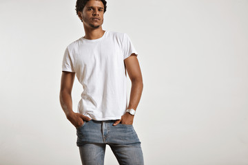 Portrait of a sensual black young model in unlabeled white t-shirt, light blue jeans and wearing a vintage digital watch