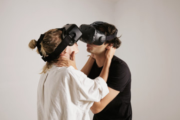 A young couple in VR headsets about to kiss, isolated on white, virtual love game