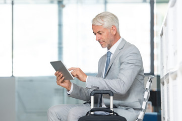 Businessman using tablet at airport