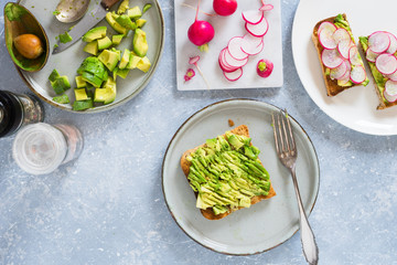 Smashed avocado on whole grain toast to make avocado and radish sandwiches