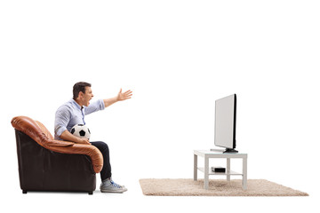 Angry man watching football on TV and shouting