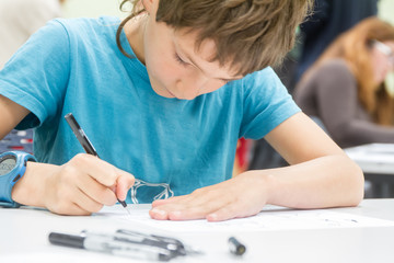 boy drawing on white paper