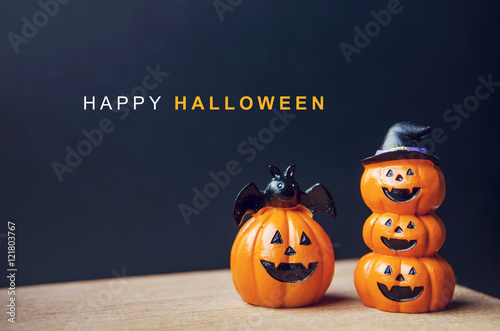 Happy Halloween message, Pumpkin on table wood with dark wall background, halloween concept.