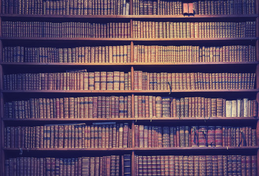 Vintage toned old books on wooden shelves, wisdom concept background.