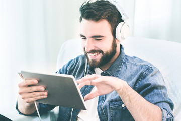 Young man video chatting on a tablet, Dressed casually in jeans, wearing headphones. Bright post processed. Urban life style, technology, online, business, shopping, fashion and job hunting concept.