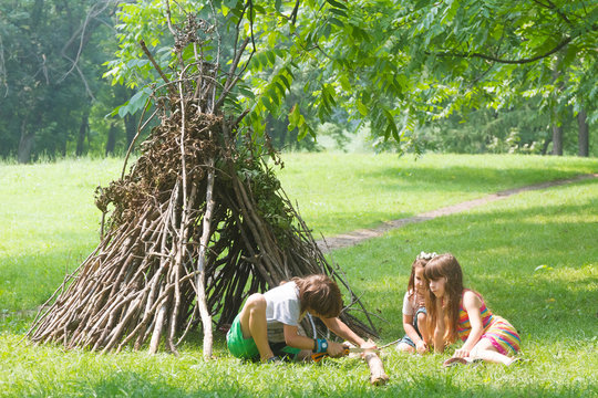 kids playing next to wooden stick house looking like indian hut,