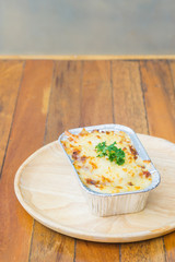 Homemade lasagne bolognese on wood table