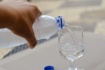 Closeup on pouring water from bottle into glass