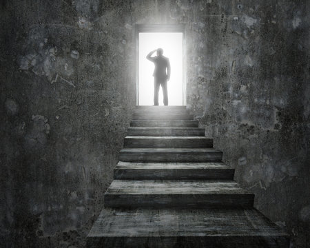 Businessman standing on top of stairs with open door