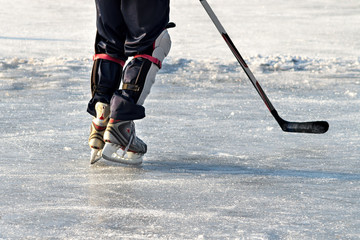 Hockey player practising on a frozen pond