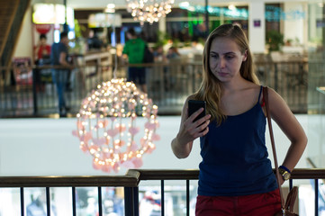 The girl looks at the phone in a shopping center