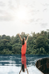 Woman in infinity pool with her hands raised