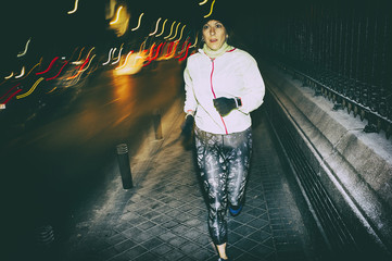 woman practicing running in the city at night