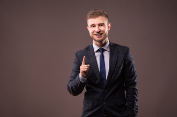 Smiling businessman standing with a smirk and a raised index fin