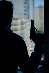 Silhouette of a man holding a gun by the window background