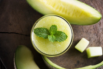 Fresh melon smoothie with almond in a glass on old wooden table background.Selective focus.