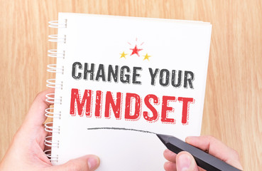 Change your mindset word on white ring binder notebook with hand