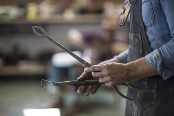 Man in workshop holding tools