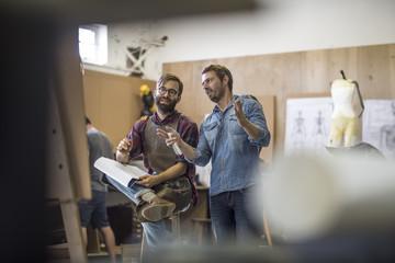 Two men in artist studio planning together