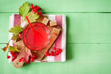 Fresh viburnum drink in glass on green wooden background with leaves and berries. Top view.