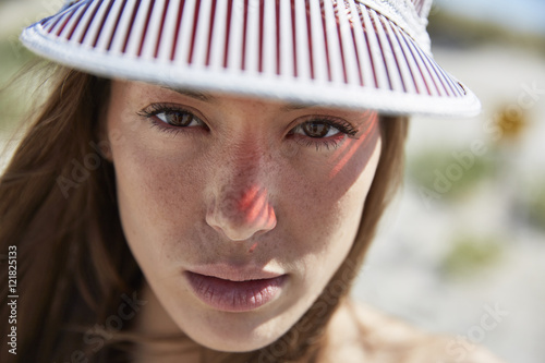 f8fefe5a Portrait of serious young woman wearing sun visor