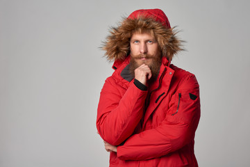 Pensive bearded man in red winter jacket