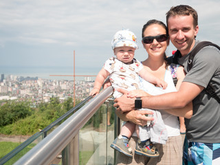 Happy family with a beautiful baby looking at the city from great height of the mountains