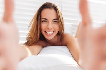 Portrait of a smiling cute woman in bikini making selfie