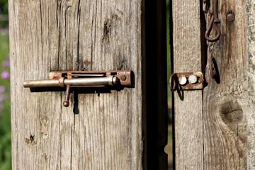 Железная ржавая щеколда на деревянной калитке