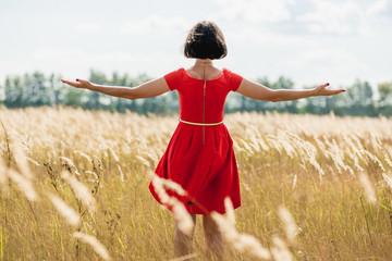girl in red dress walking on the field