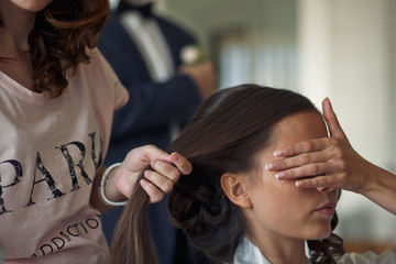 The barber makes hairstyle for bride