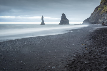 lava beach and two rocks in water in Iceland