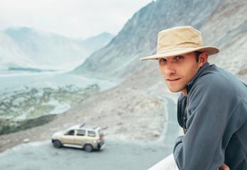 Auto traveler has a break time on mountain road