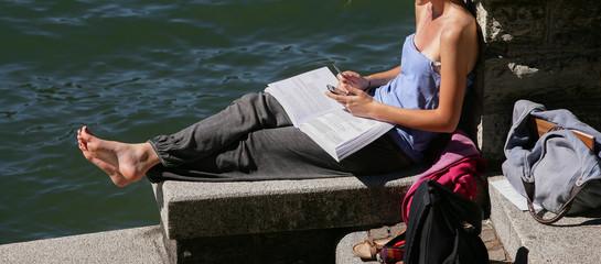 Ragazza a piedi nudi, legge  sulla riva del lago